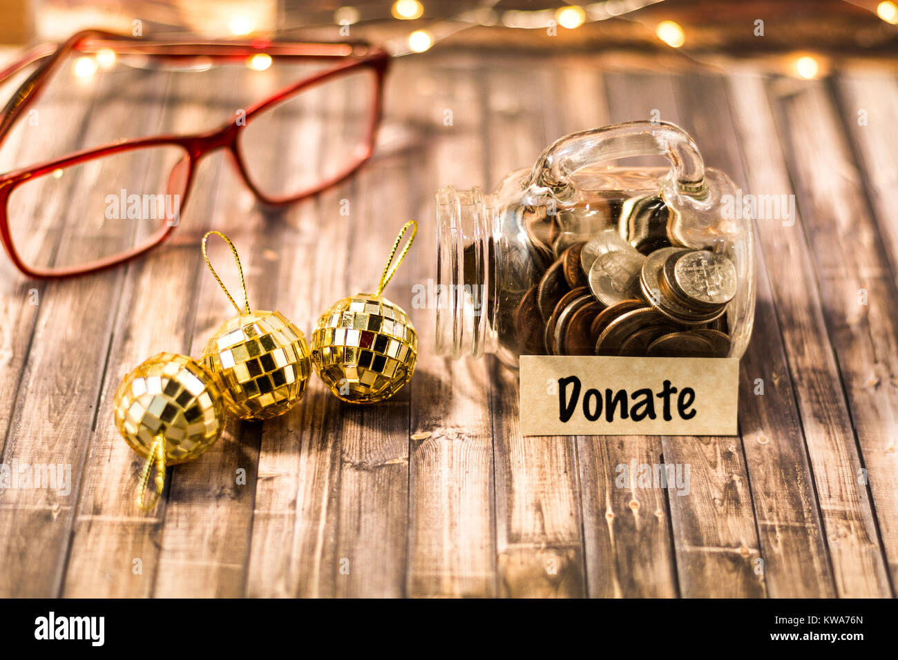 Donate money jar savings plan and giving motivational concept on wooden board - Stock Image