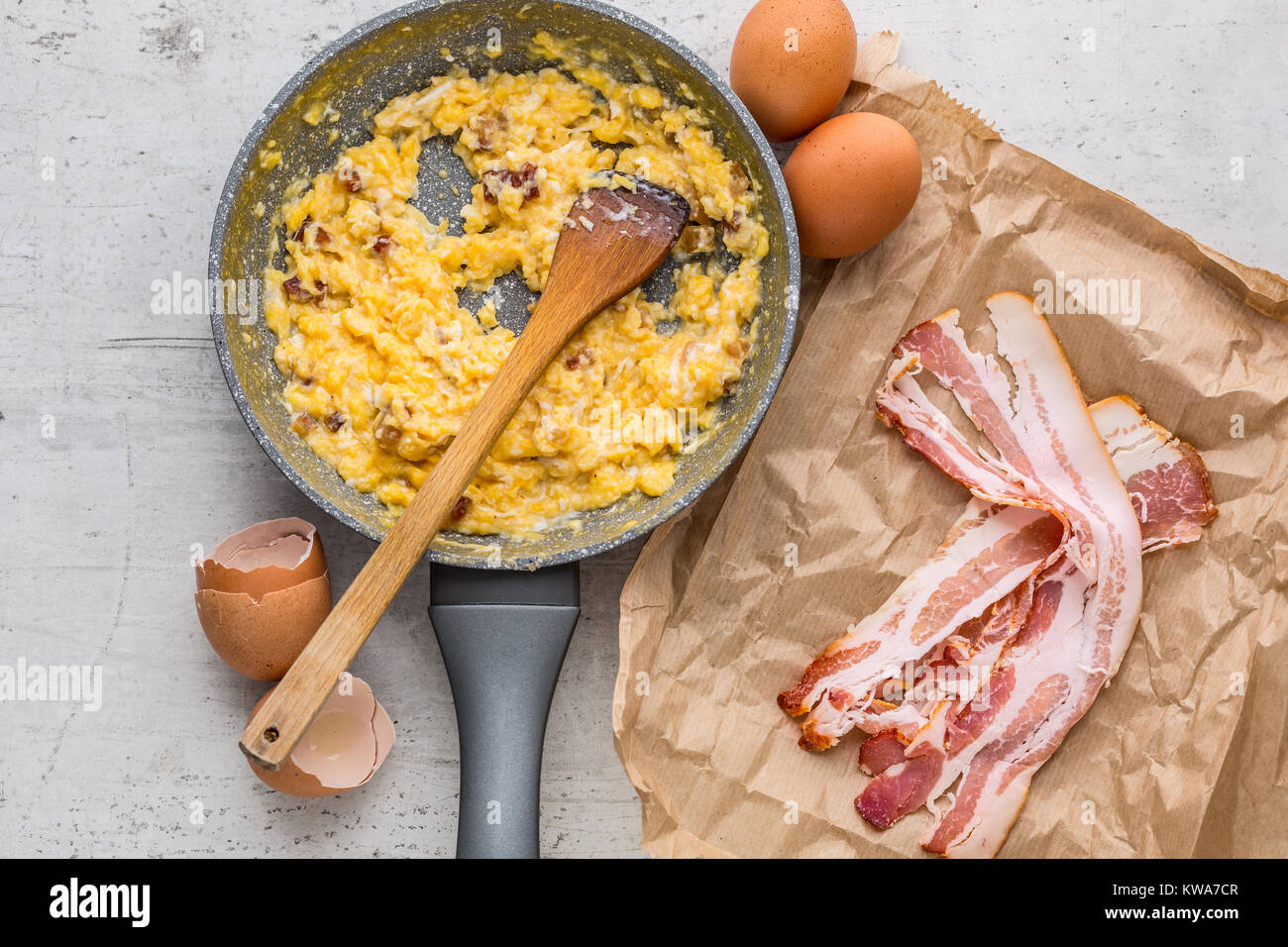 Ham and eggs. Scrambled eggs with bacon in ceramic pan. - Stock Image