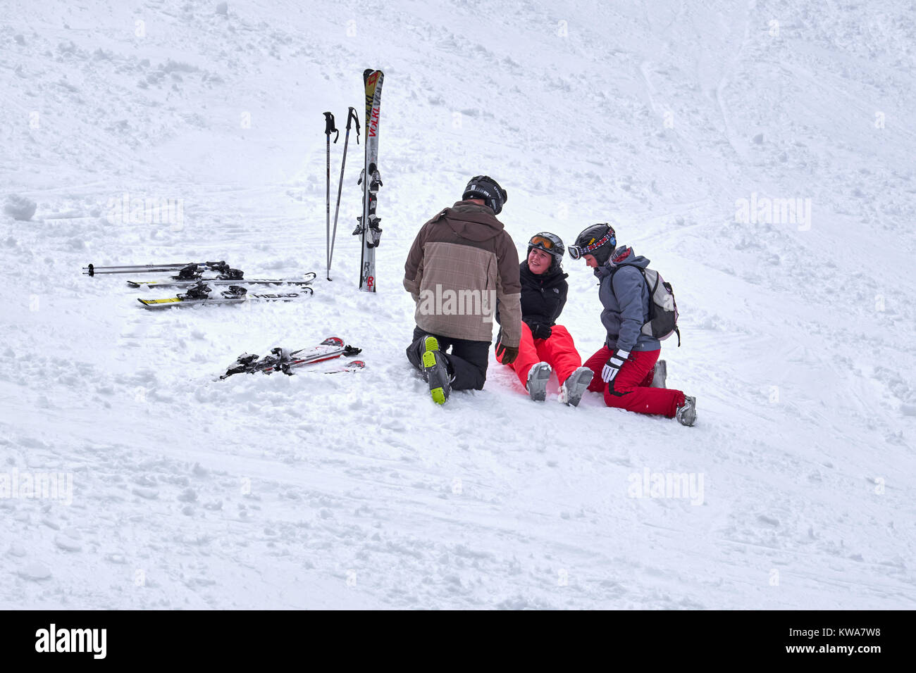 WINTERBERG, GERMANY - FEBRUARY 16, 2017: Woman sitting on a ski slope with injured leg being taken care of at Ski - Stock Image