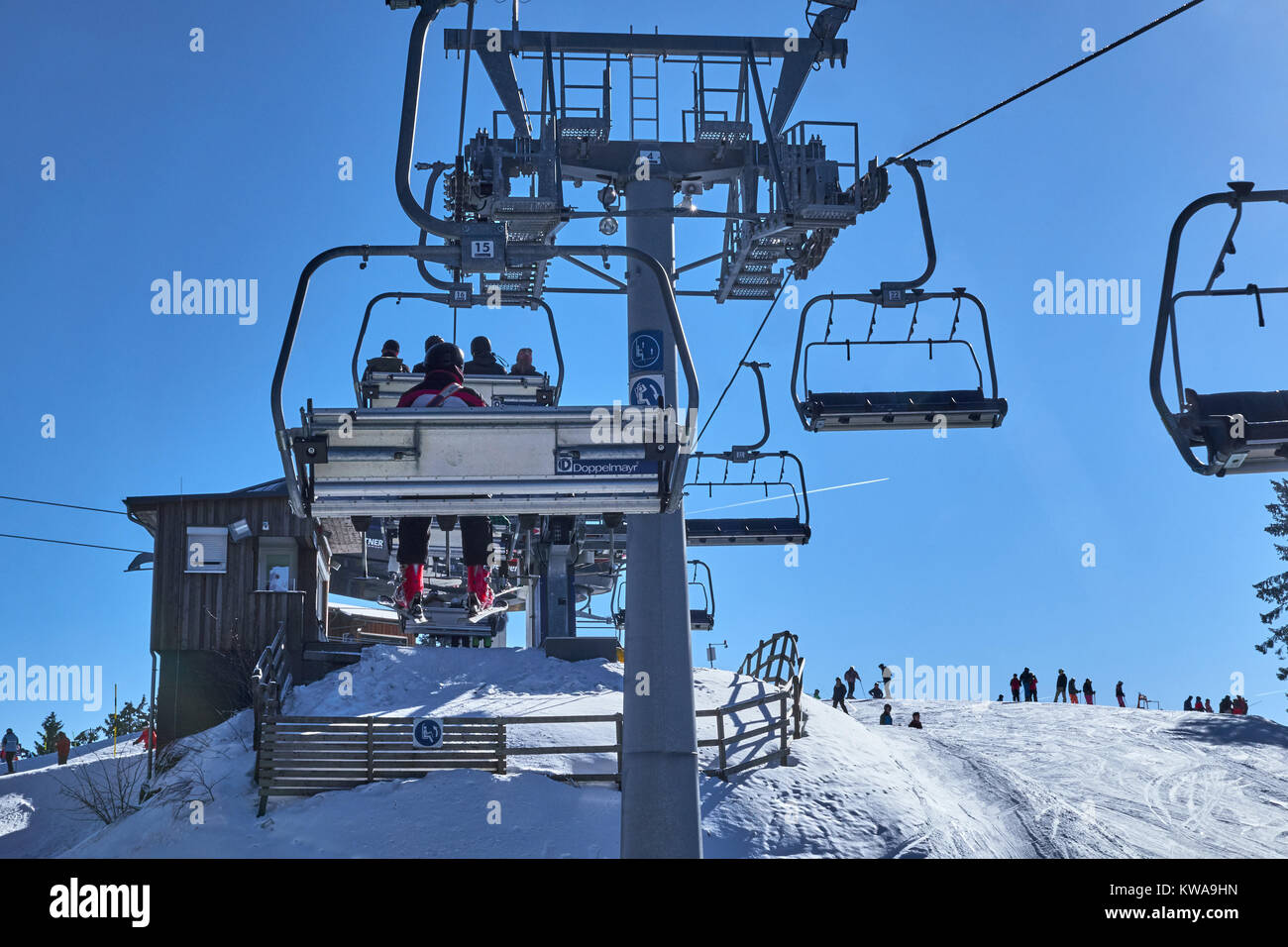 WINTERBERG, GERMANY - FEBRUARY 14, 2017: People sitting up high above the pistes in a chairlift at Ski Carousel - Stock Image