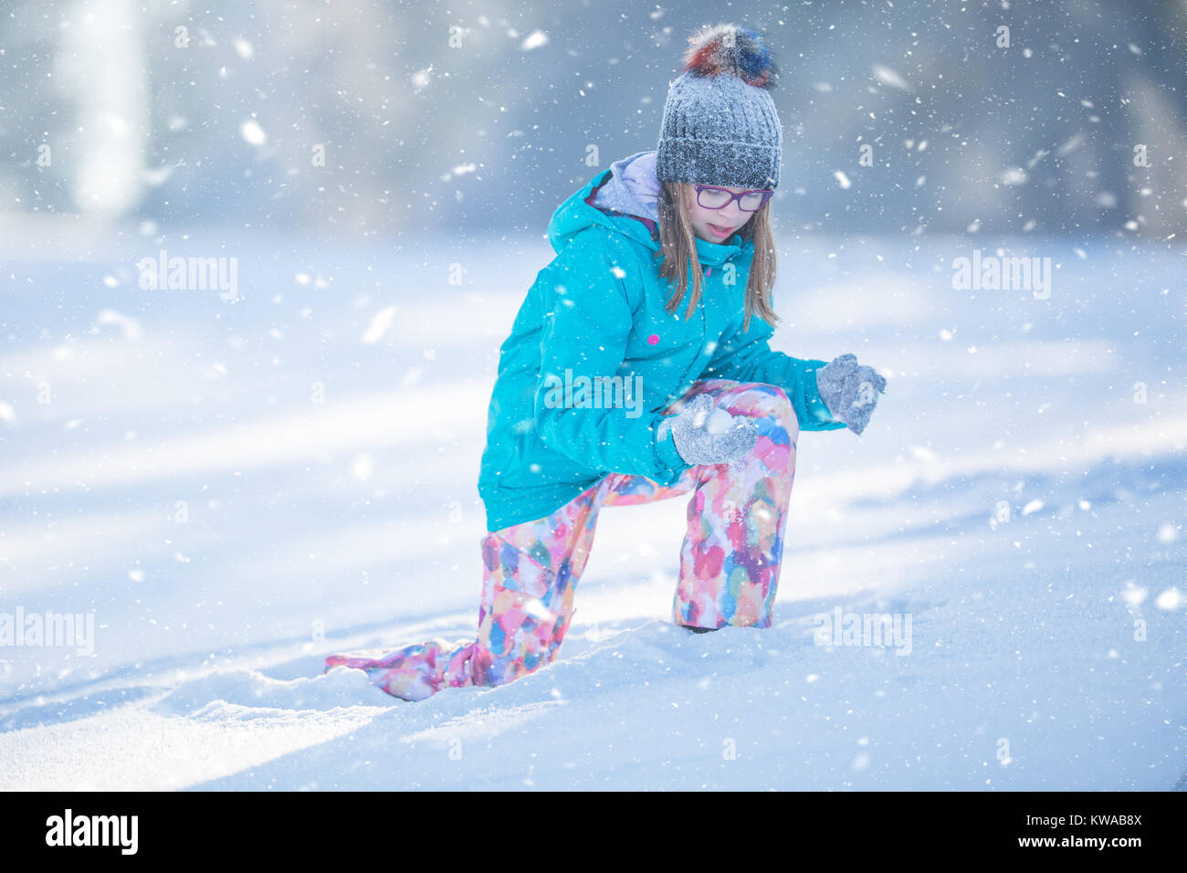 Happy young Pre-Teen girl in warm clothing  playing with snow. Stock Photo