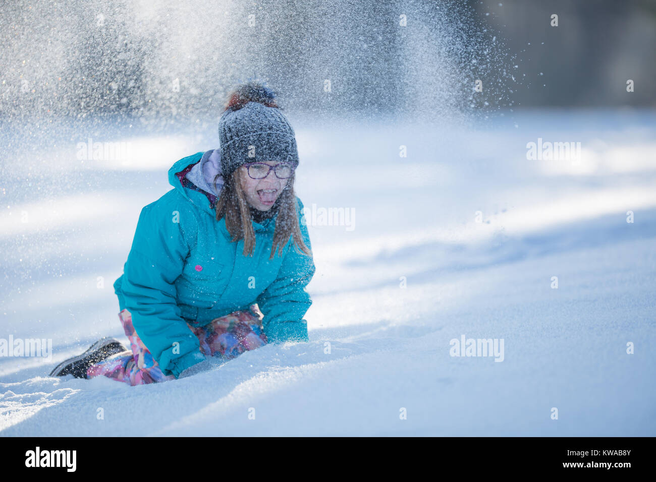 Happy young Pre-Teen girl in warm clothing  playing with snow. - Stock Image