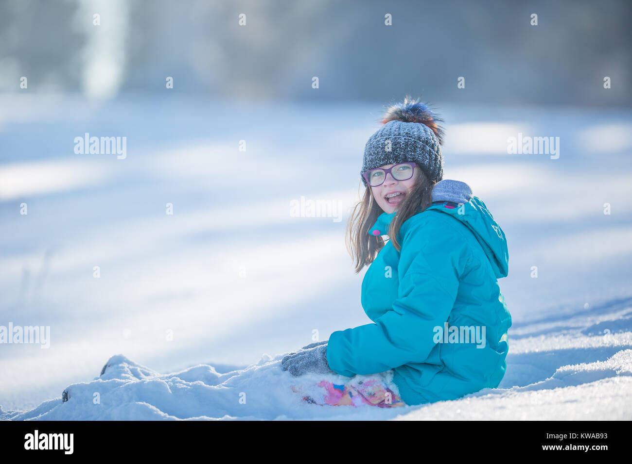 ed737ed584c2 Happy young Pre-Teen girl in warm clothing playing with snow Stock ...