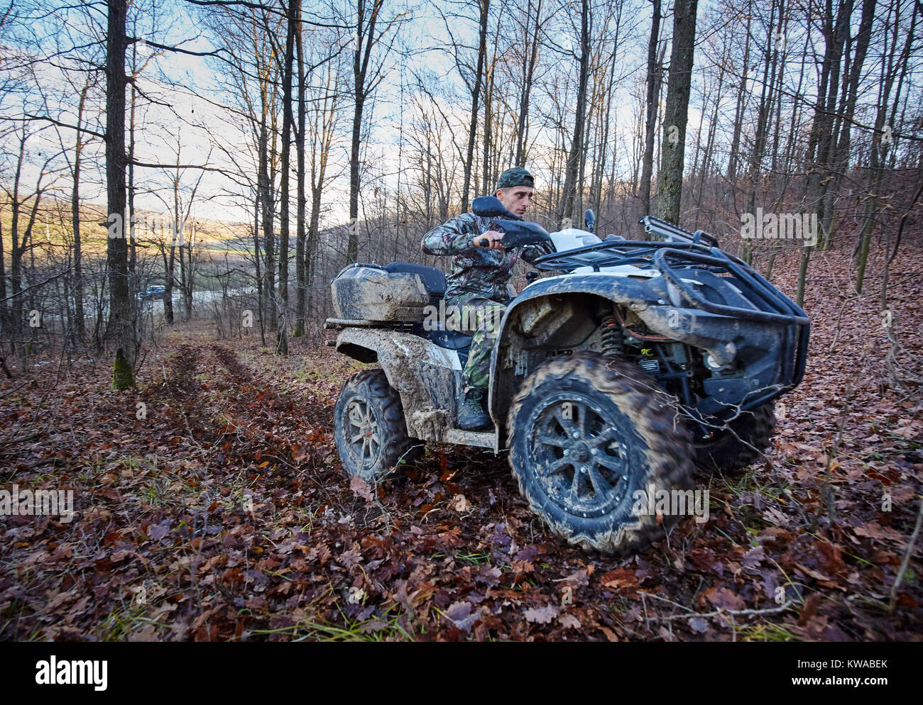 Young hunter on a quad bike searching for game in the forest - Stock Image
