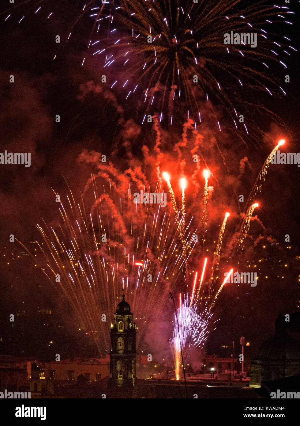 Fireworks explode over the San Felipe Neri church in the colonial center on the stoke of midnight celebrating the - Stock Image