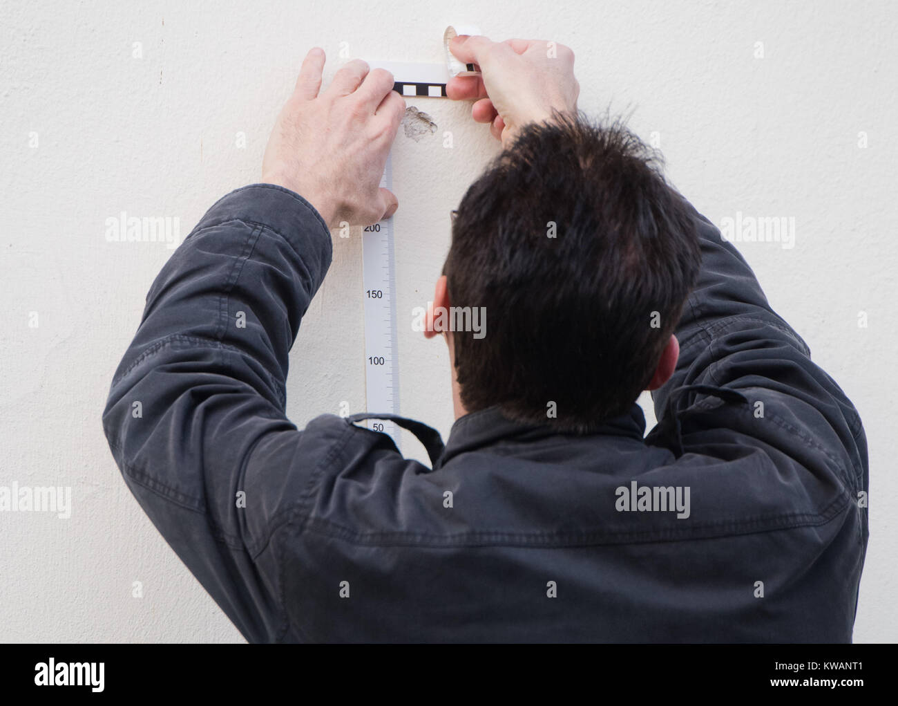 Salzgitter, Germany. 2nd Jan, 2018. A member of the crime scene unit of the police takes probes from a damaged wall, - Stock Image