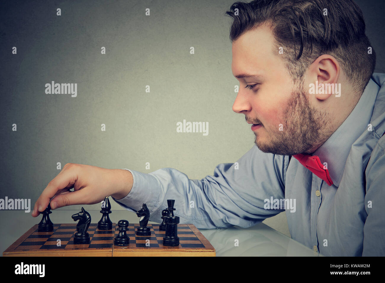 Young chunky man concentrated on building strategy while playing chess. Stock Photo