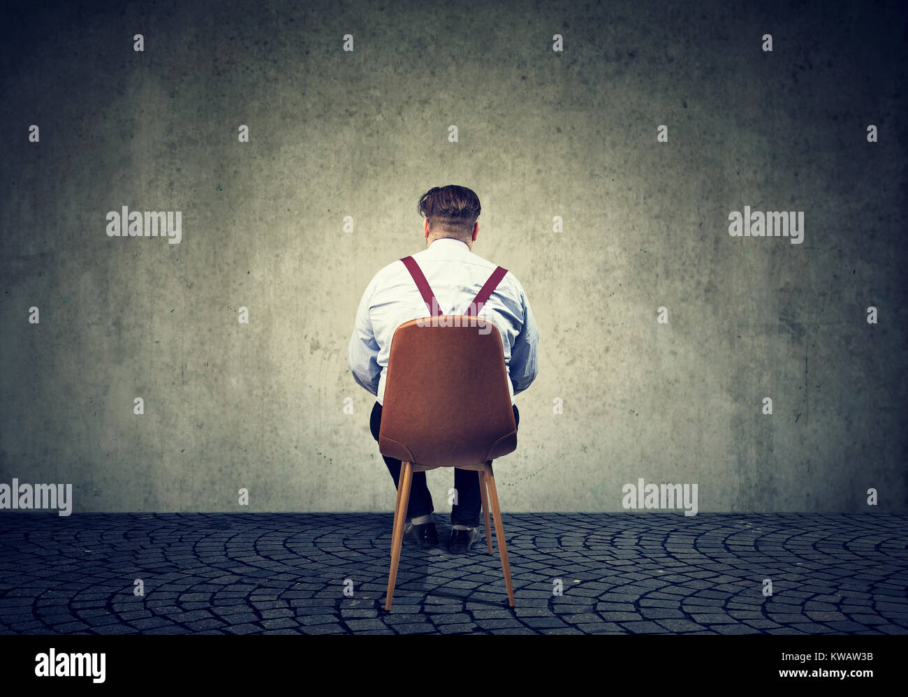 Back view of man sitting on chair looking at concrete gray wall having problems. - Stock Image