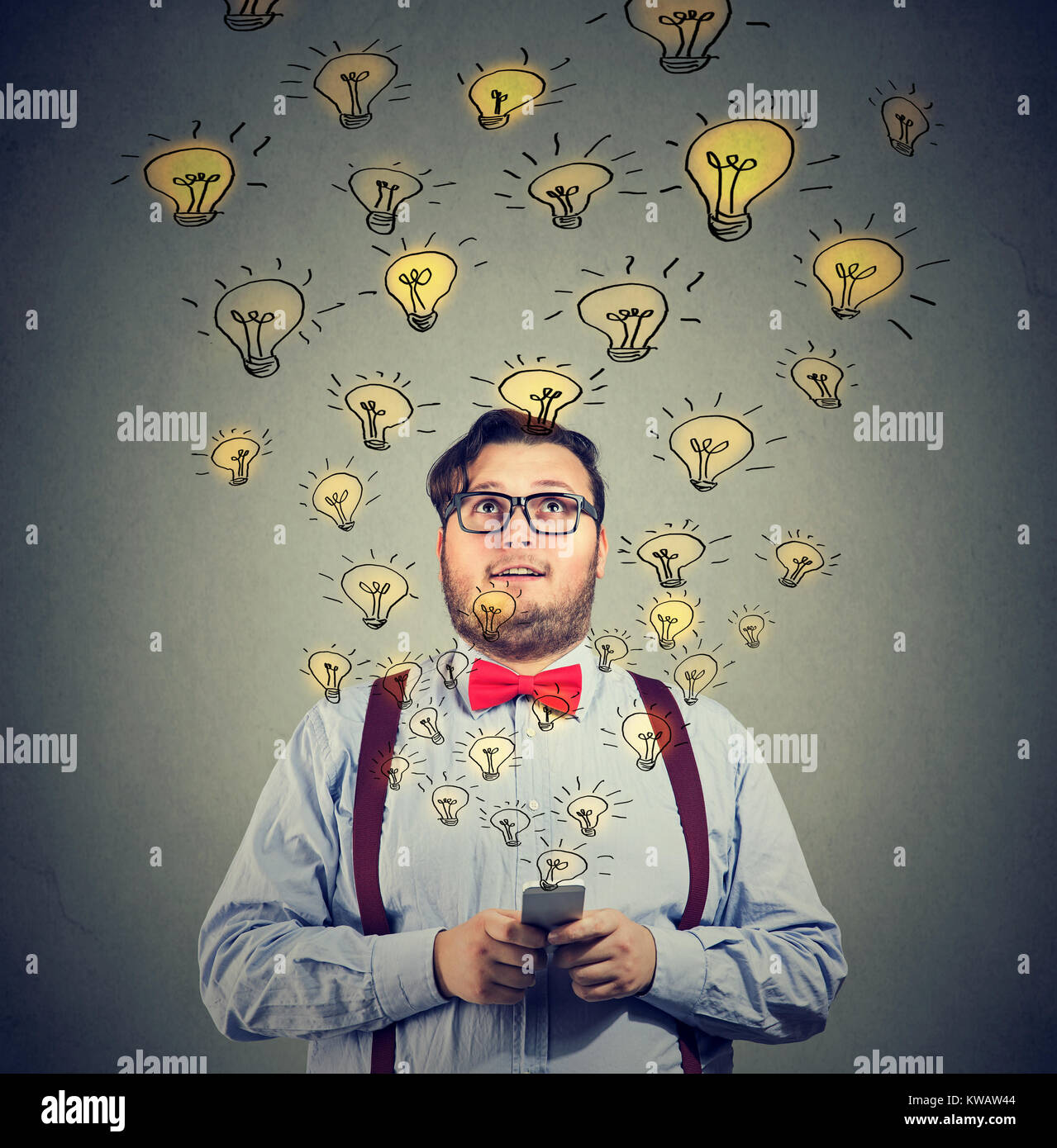 Young excited man holding smartphone sharing with bright ideas looking content. - Stock Image