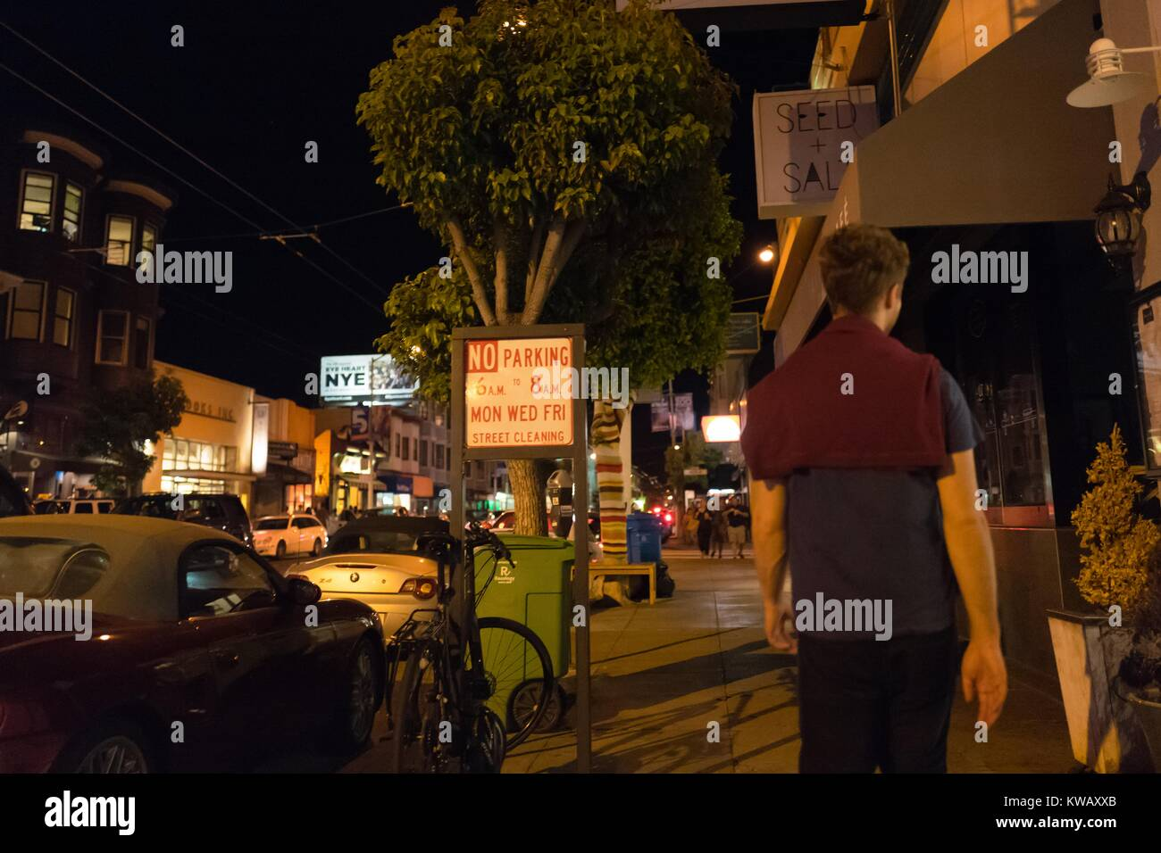 A man who has a maroon sweater draped over his shoulders stands on the sidewalk, San Francisco, California, October - Stock Image