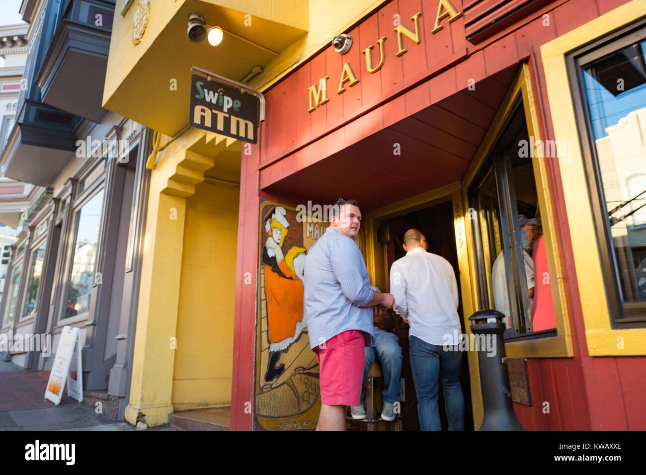 A doorman is checking the IDs of two men entering the Mauna Loa Club in San Francisco, California, October 8, 2016. - Stock Image