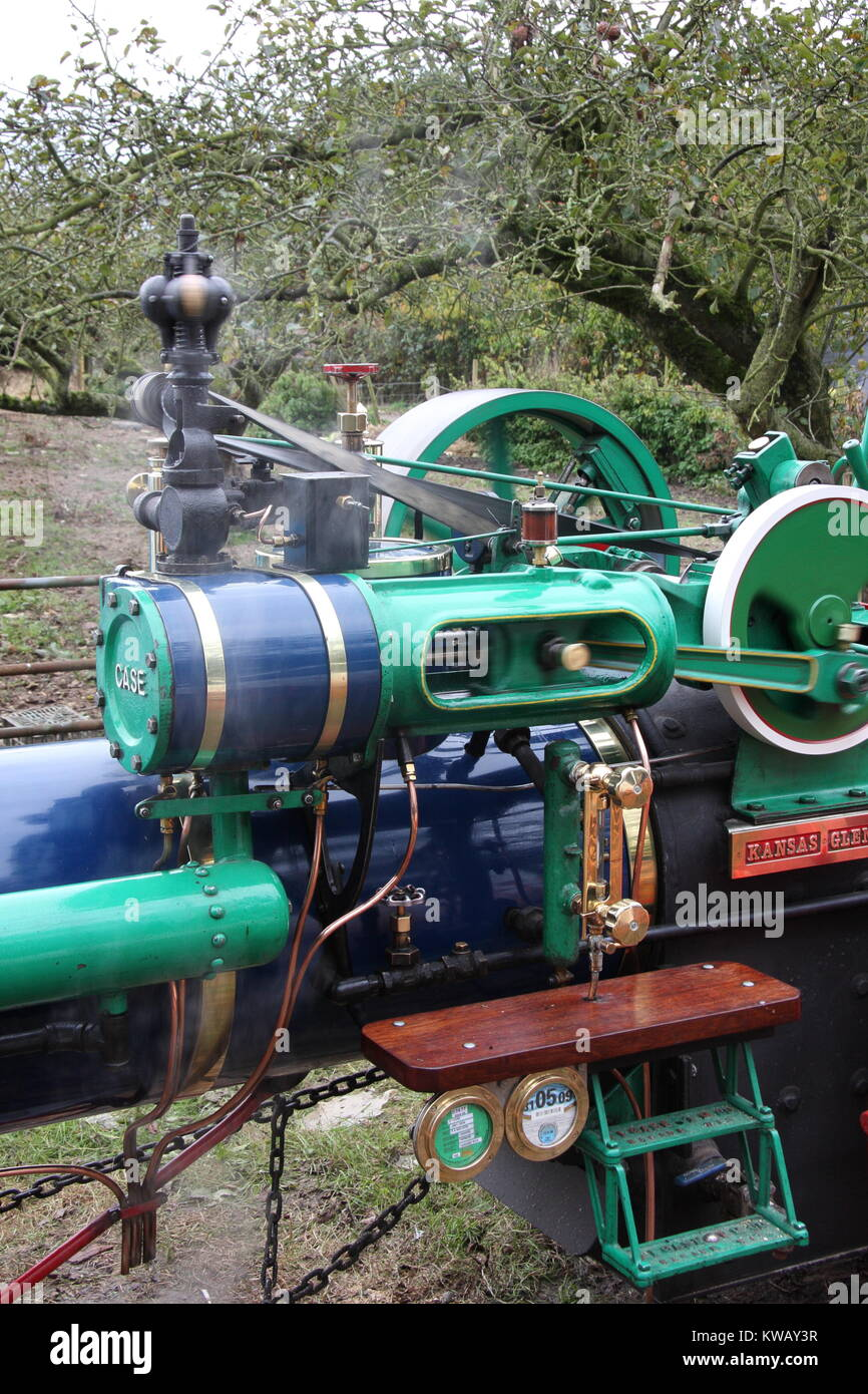 close up of a half size stream engine with an orchard behind, the engine is fired up. Part of a bygone age, in farming - Stock Image