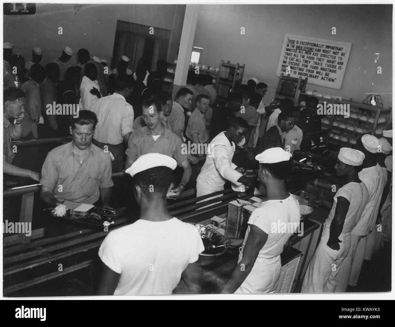 Men stand in lines in the mess hall for naval barracks in Hastings, Nebraska, 1944. - Stock Image
