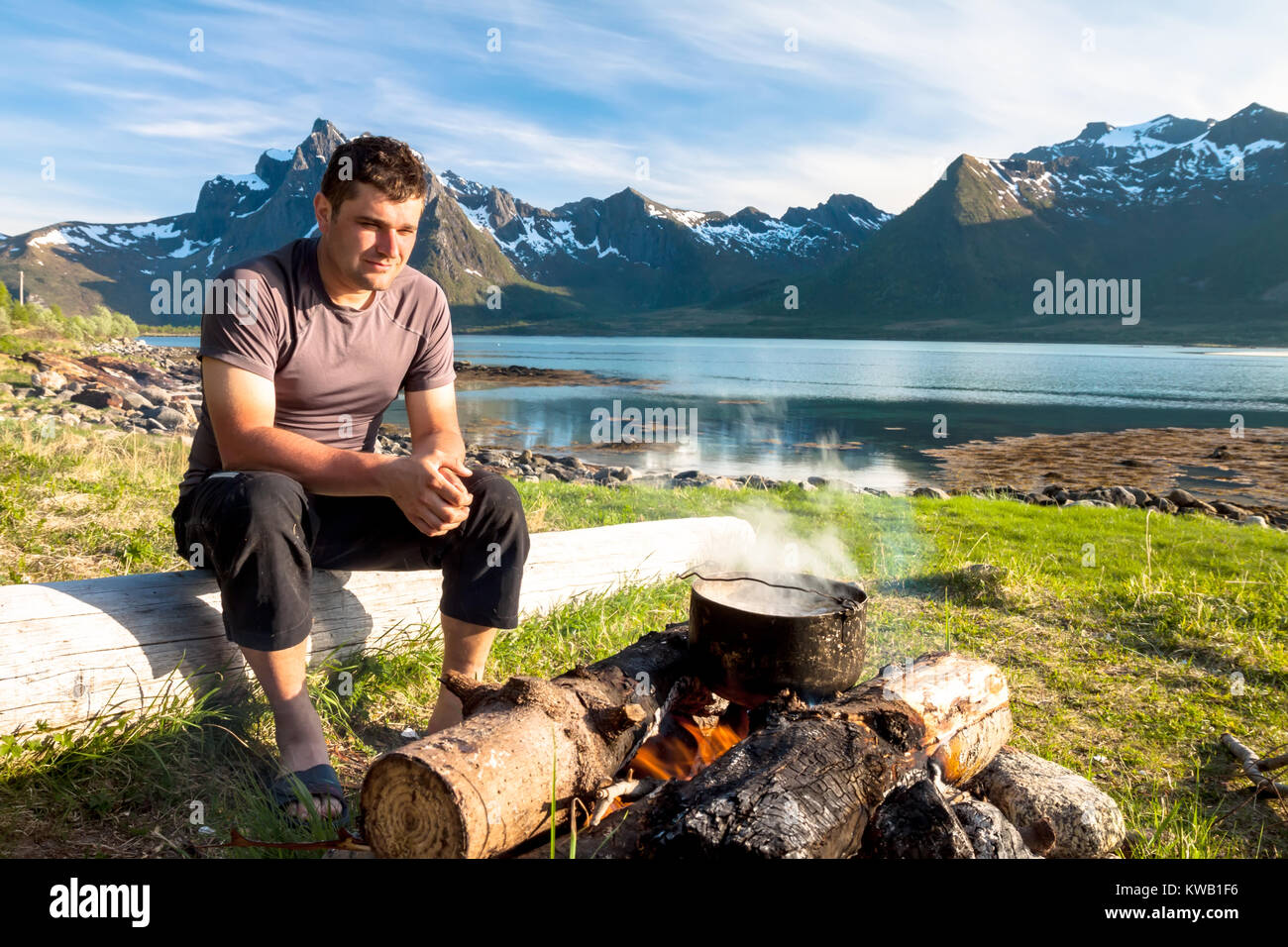 Man and campfire at sunset - Stock Image