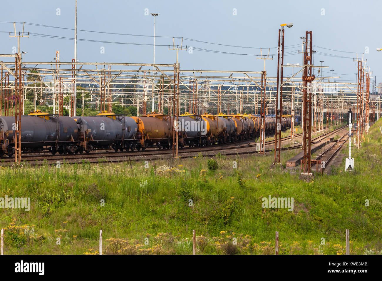 Train with cargo pulls into station transporting jet fuel tankers. - Stock Image