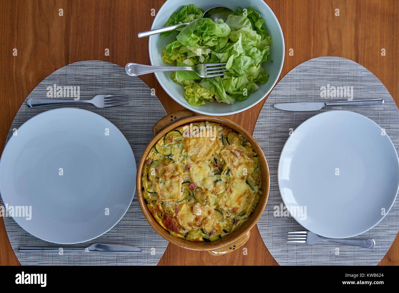 Zucchini Flan Gratined With Belgian Cheese Herve Served On a Dressed Table With Salad - Stock Image