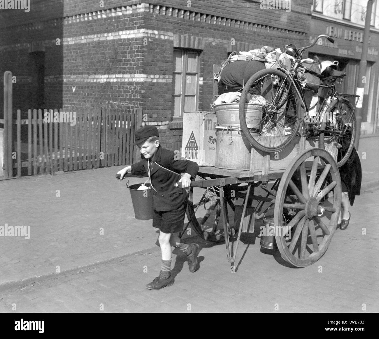 A boy pulls, as his mother pushes, a cart loaded with their possessions in Uerdingen, Germany. U.S. Army evacuated - Stock Image