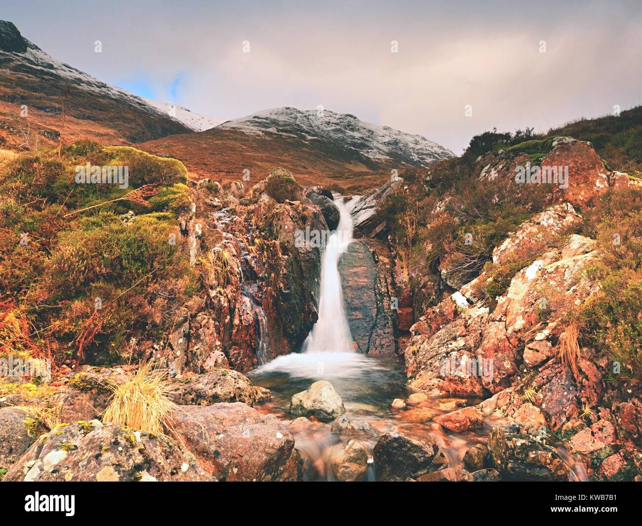 Mountains landscape wild stream in front. White snowy mountain peaks and grey cloudy sky - Stock Image