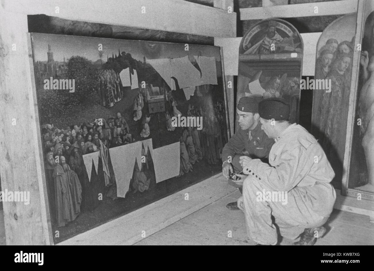 Soldiers of U.S. Army MFAA Section examining the Ghent Altarpiece in the Altaussee mine, 1945. Lt. Daniel J. Kern Stock Photo