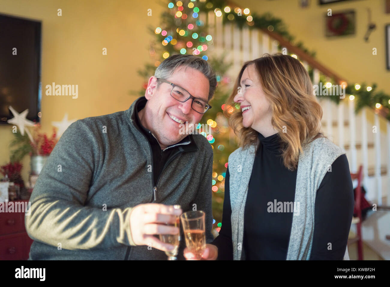 happy couple smiling and drinking champagne in front of christmas tree at home stock image