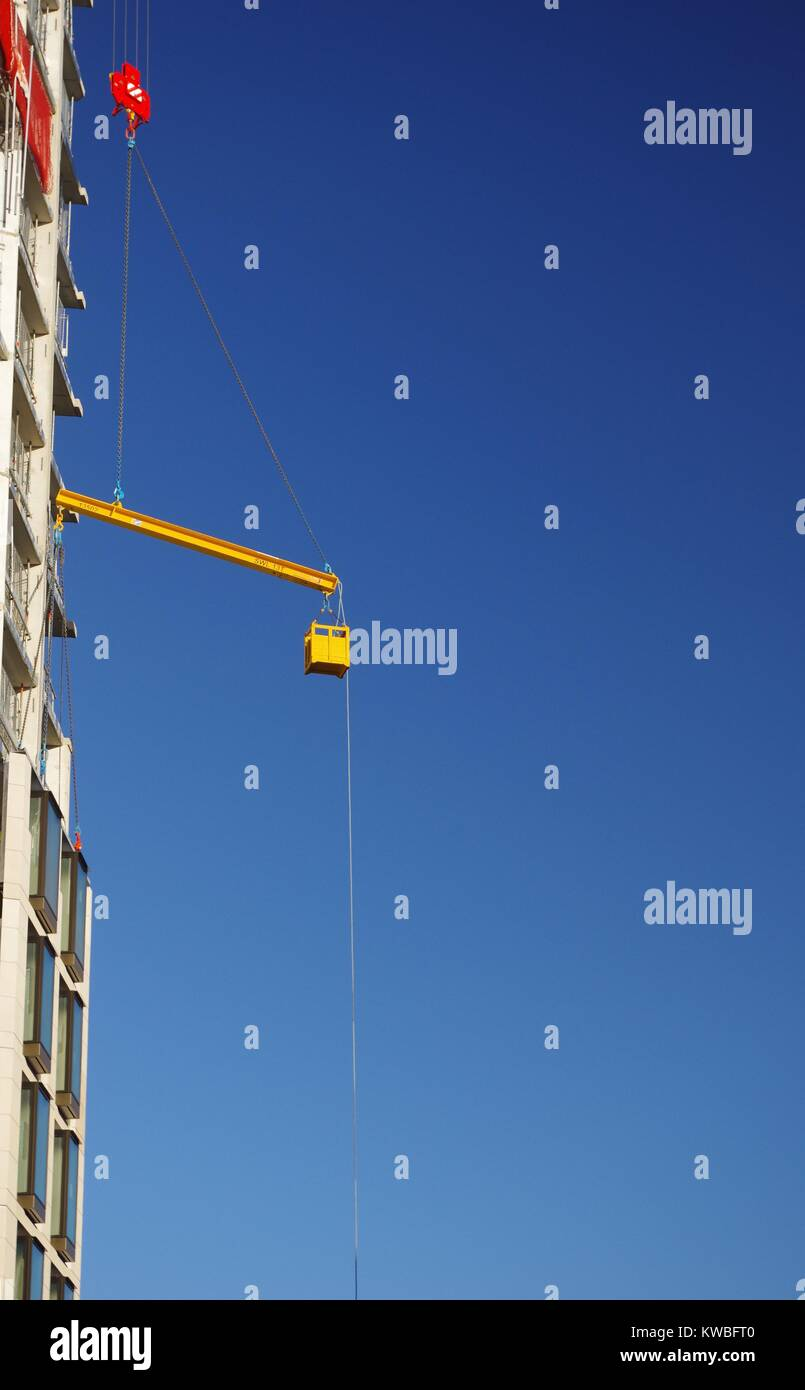 Yellow Suspended Steel Beam being Hoisted by a Crane against a Blue Sky. London Building Site. UK. Stock Photo
