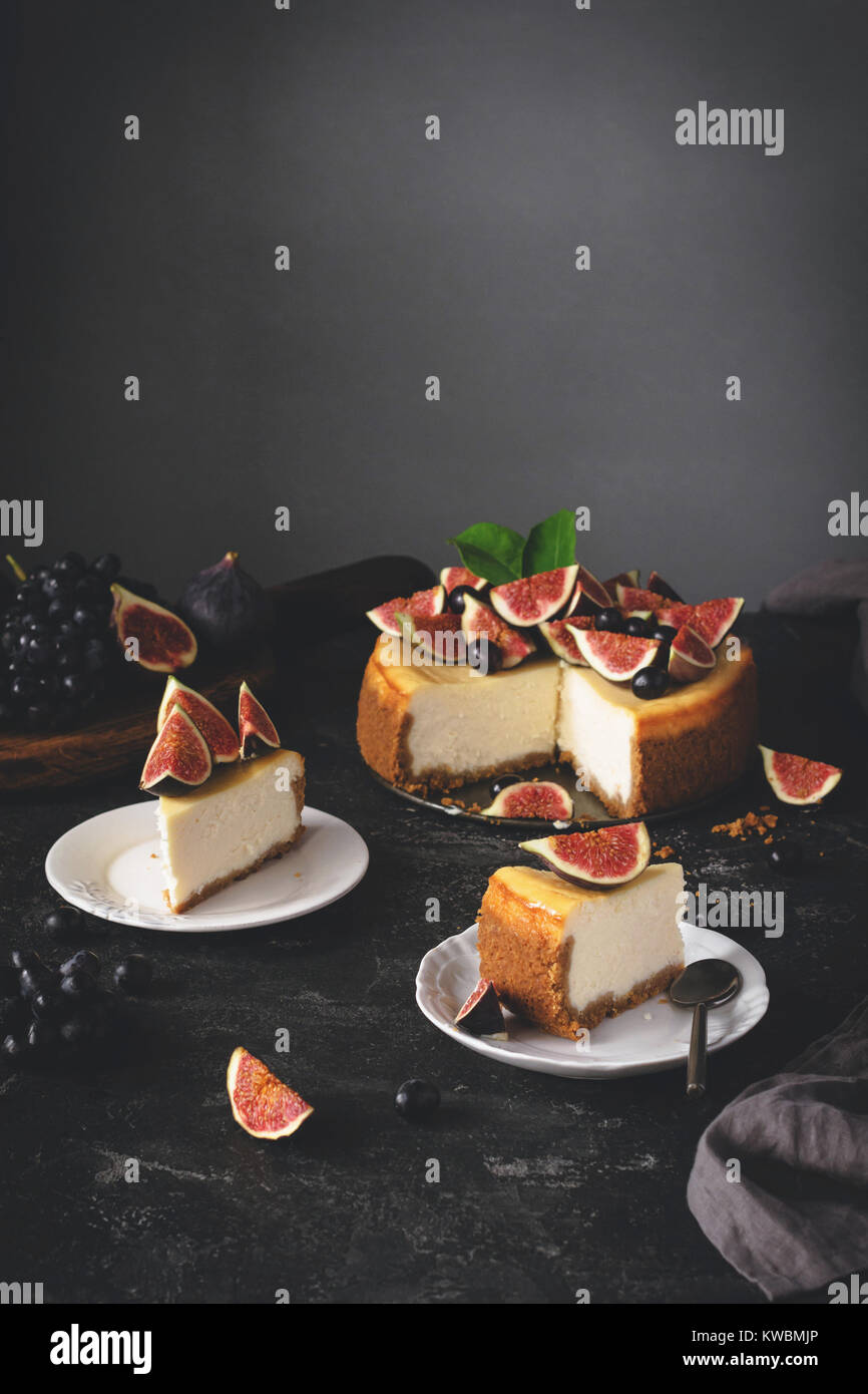 Cheesecake with figs. Sliced New York Cheesecake on dark stone background. Selective focus, toned image - Stock Image