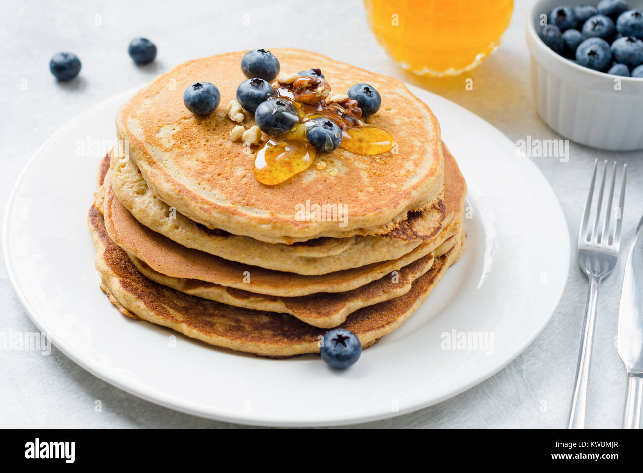 Closeup view of pancakes stack with blueberries, walnuts and honey on white plate. Tasty healthy breakfast food. Stock Photo