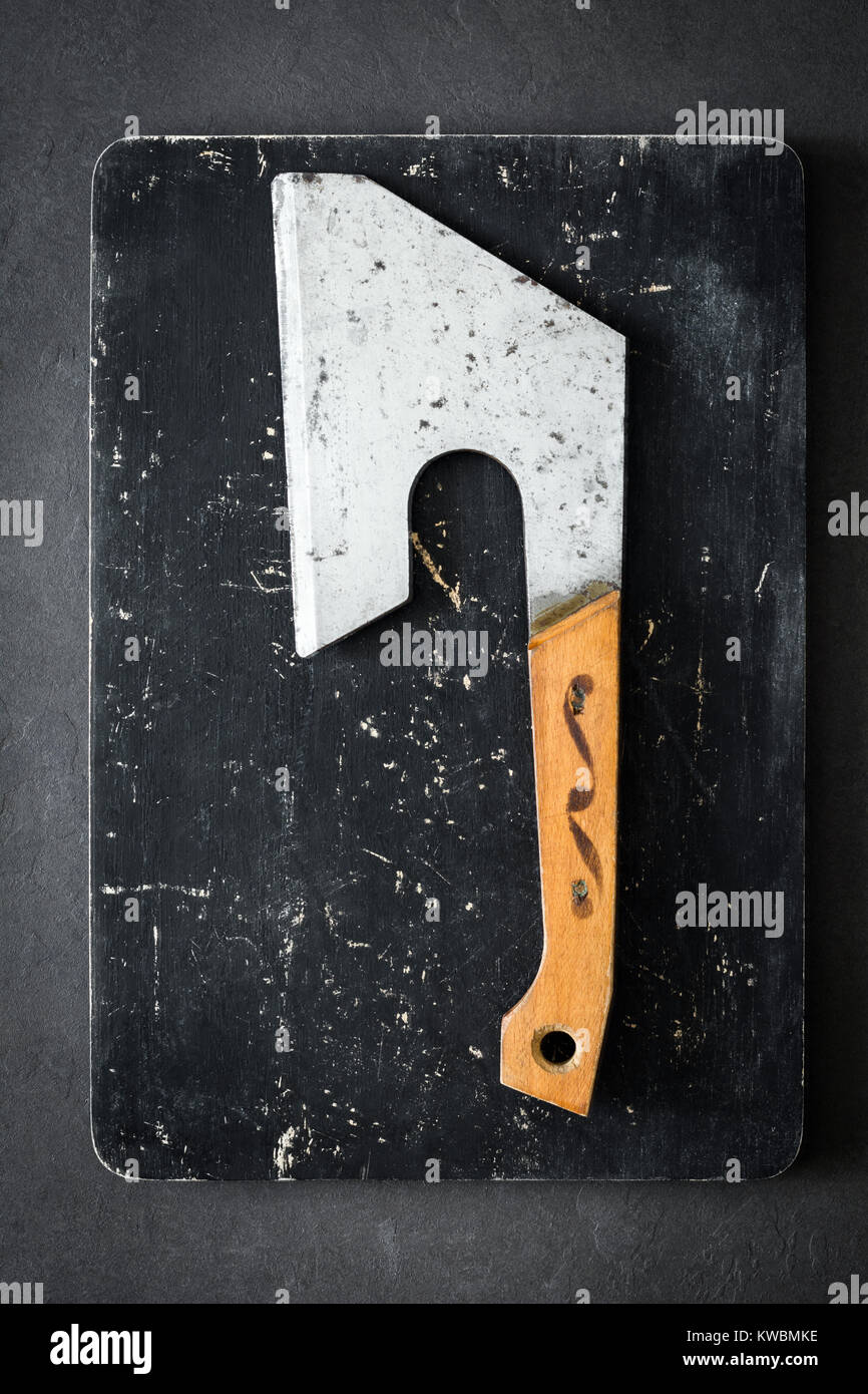 Old butcher axe or meat cleaver on black cutting board. Vertical, top view - Stock Image