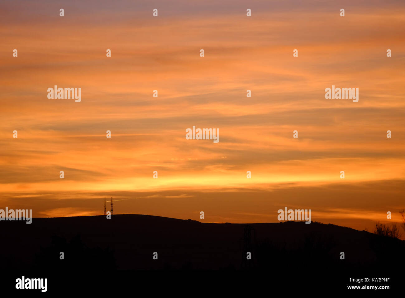 Radio masts on the south downs near Firle, East Sussex, at sunset. - Stock Image