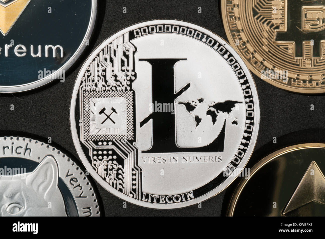 Litecoin cryptocurrency real silver coin in middle of other crypto closeup Stock Photo
