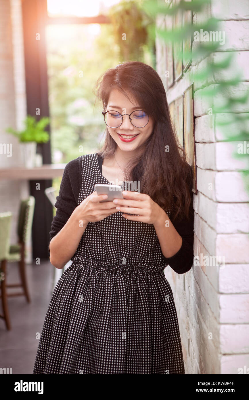 asian younger woman toothy smiling face reading message in smart phone - Stock Image