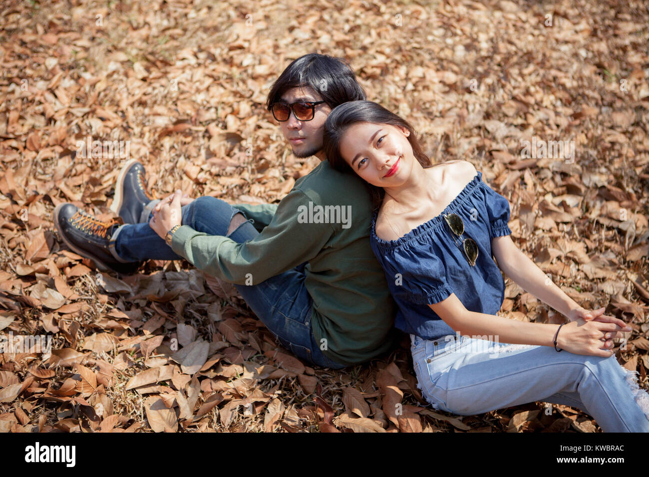 portrait of younger asian man and woman relaxing on dry leaves on ground - Stock Image