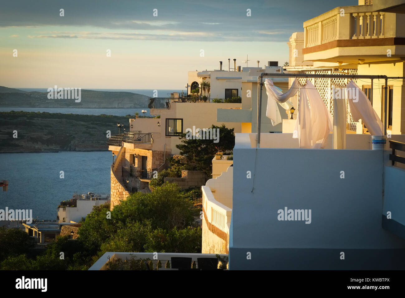 Washing drying on a balcony in Mellieha, Malta, evening light, with the sea behind - Stock Image