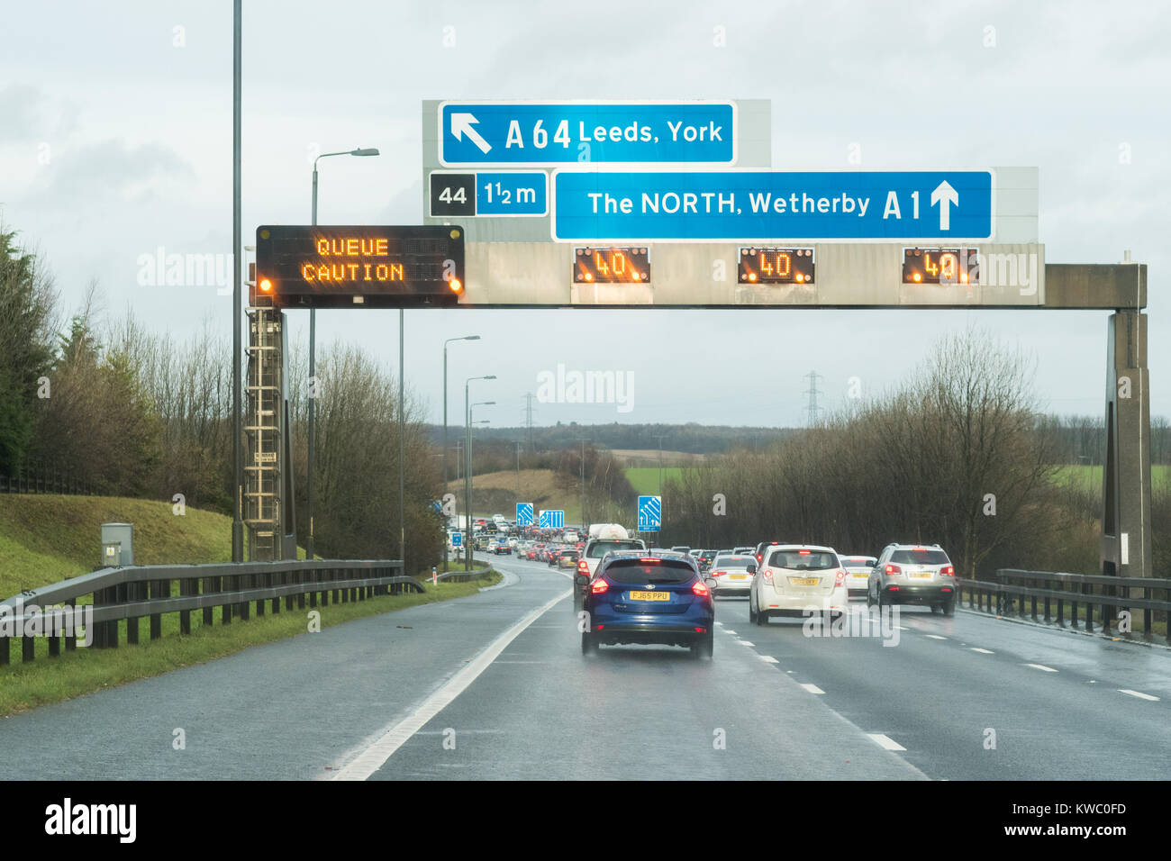 UK motorway gantry sign with warning and speed restriction where M1 motorway and A1M merge heading north - Stock Image