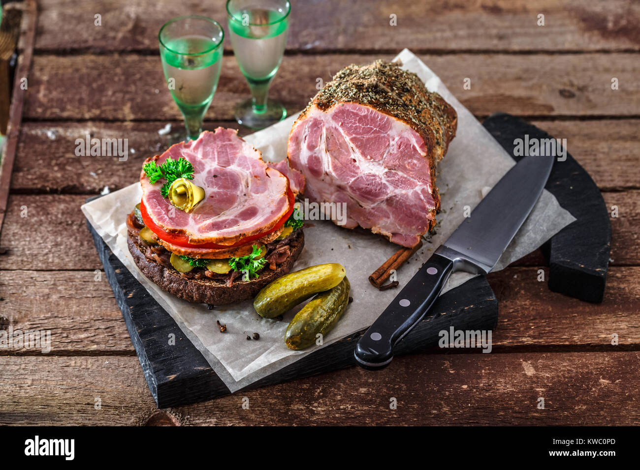 Delicious rye sandwich with smoked ham, tomato, onion jam, pickles and vodka. - Stock Image