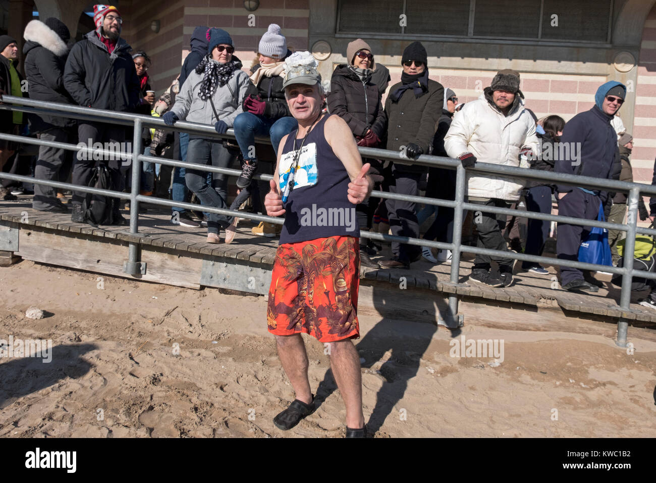 A Polar Bear Club member with spectators behind him at the 114th Polar Bear Club New Year's Day swim. - Stock Image