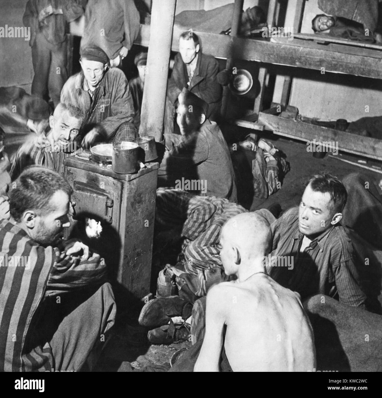 Sandbostel Prison camp survivors sit around a stove fire after British Liberation, April 30, 1945. They were among - Stock Image