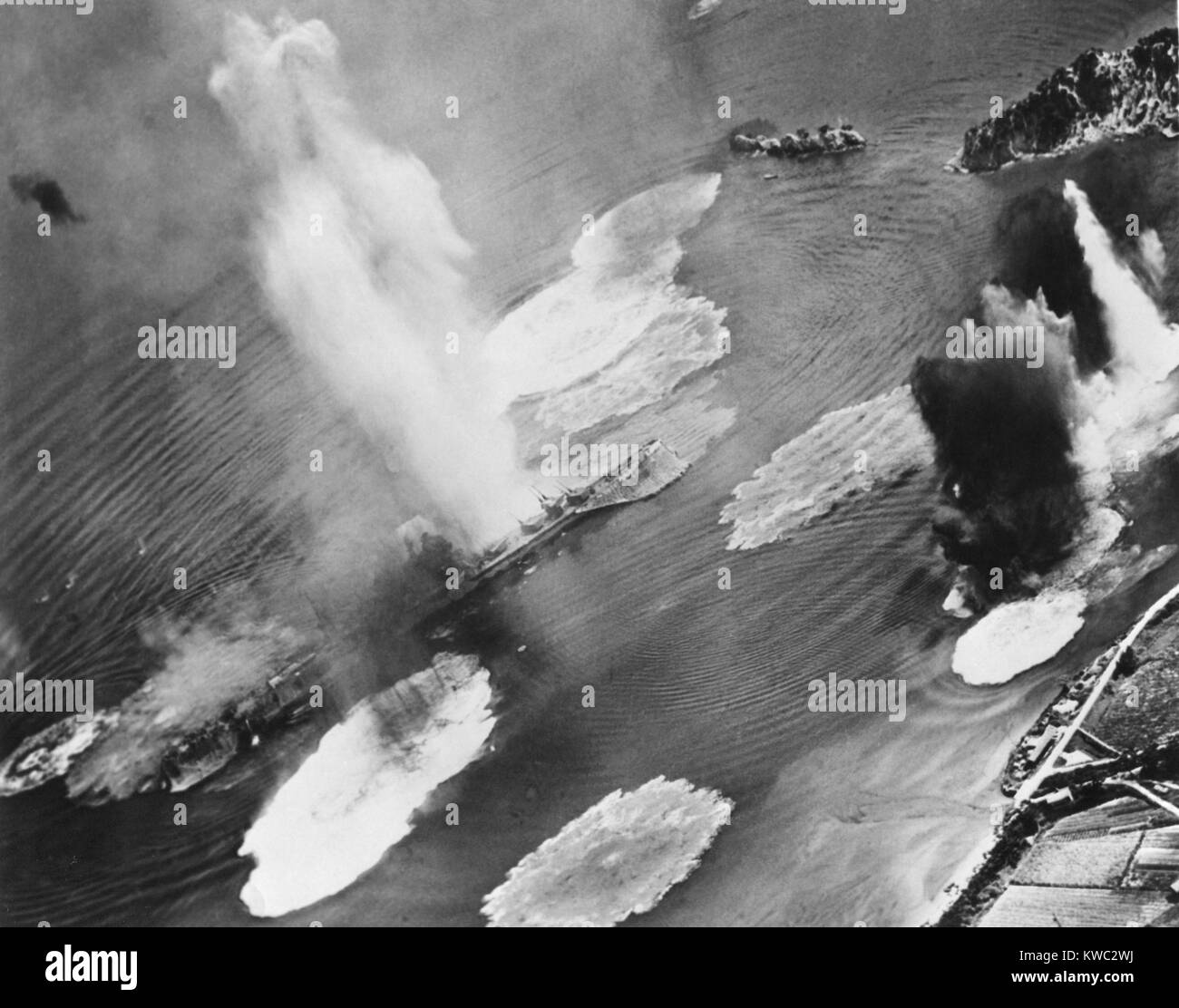 U.S. carrier planes bomb Japanese cruisers anchored in the Kure Harbor Naval Base at Honshu. The warship under attack - Stock Image