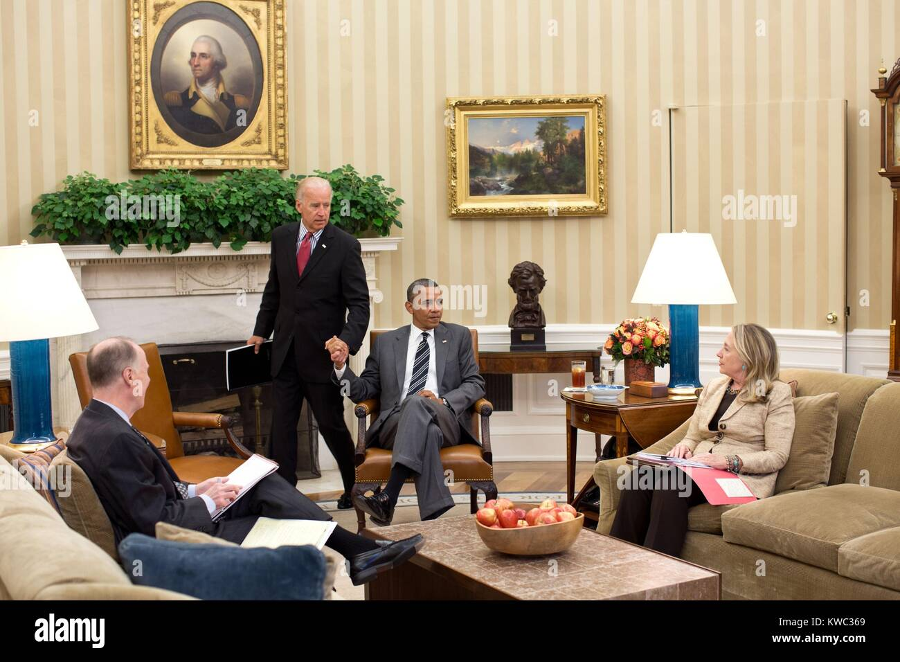 VP Joe Biden and Pres. Obama grip hands as he arrives for a meeting in the Oval Office. Already seated are Sec. - Stock Image