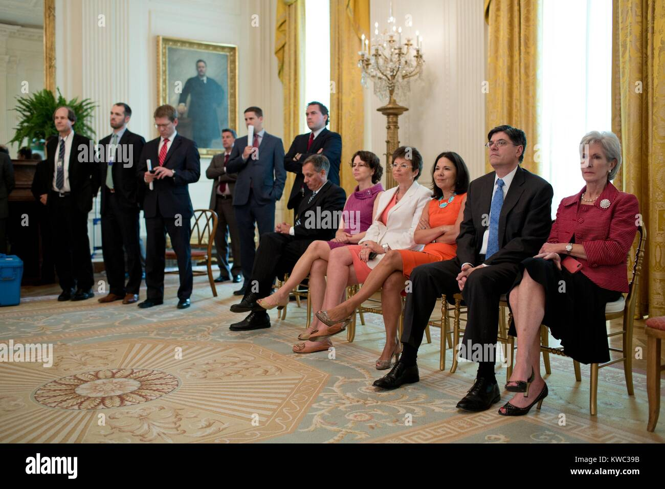 President Obama's staff listen as he broadcasts remarks about Supreme Court's ruling on 'Obama Care'. - Stock Image