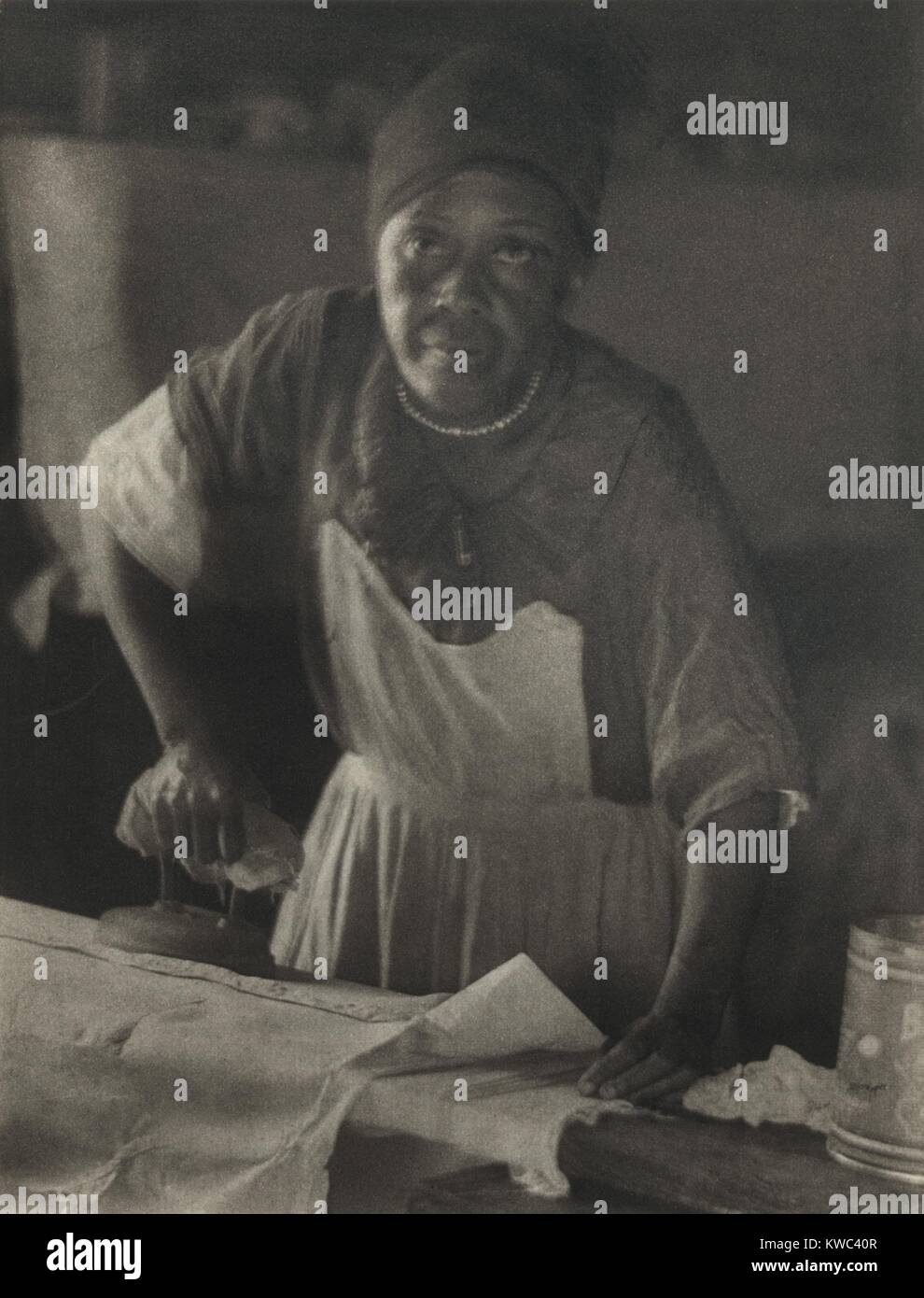 African American woman ironing, ca. 1930. Photogravure of image by Doris Ulmann. She is best known for her sensitive - Stock Image