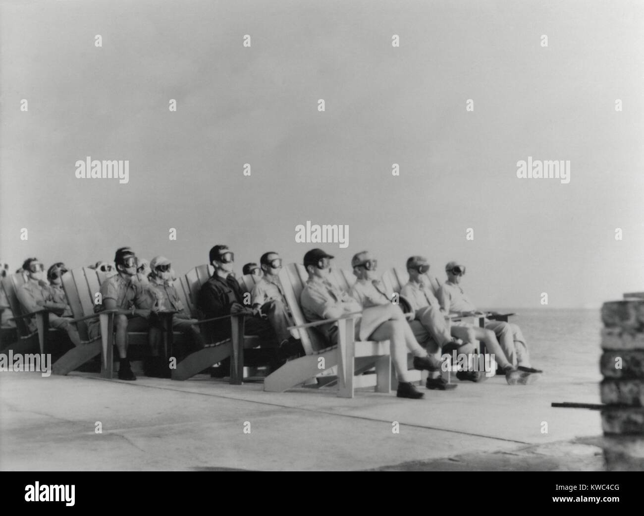 VIPs view the DOG shot, an 81 kiloton atomic detonation wearing safety goggles. They are sitting on Adirondack chair Stock Photo