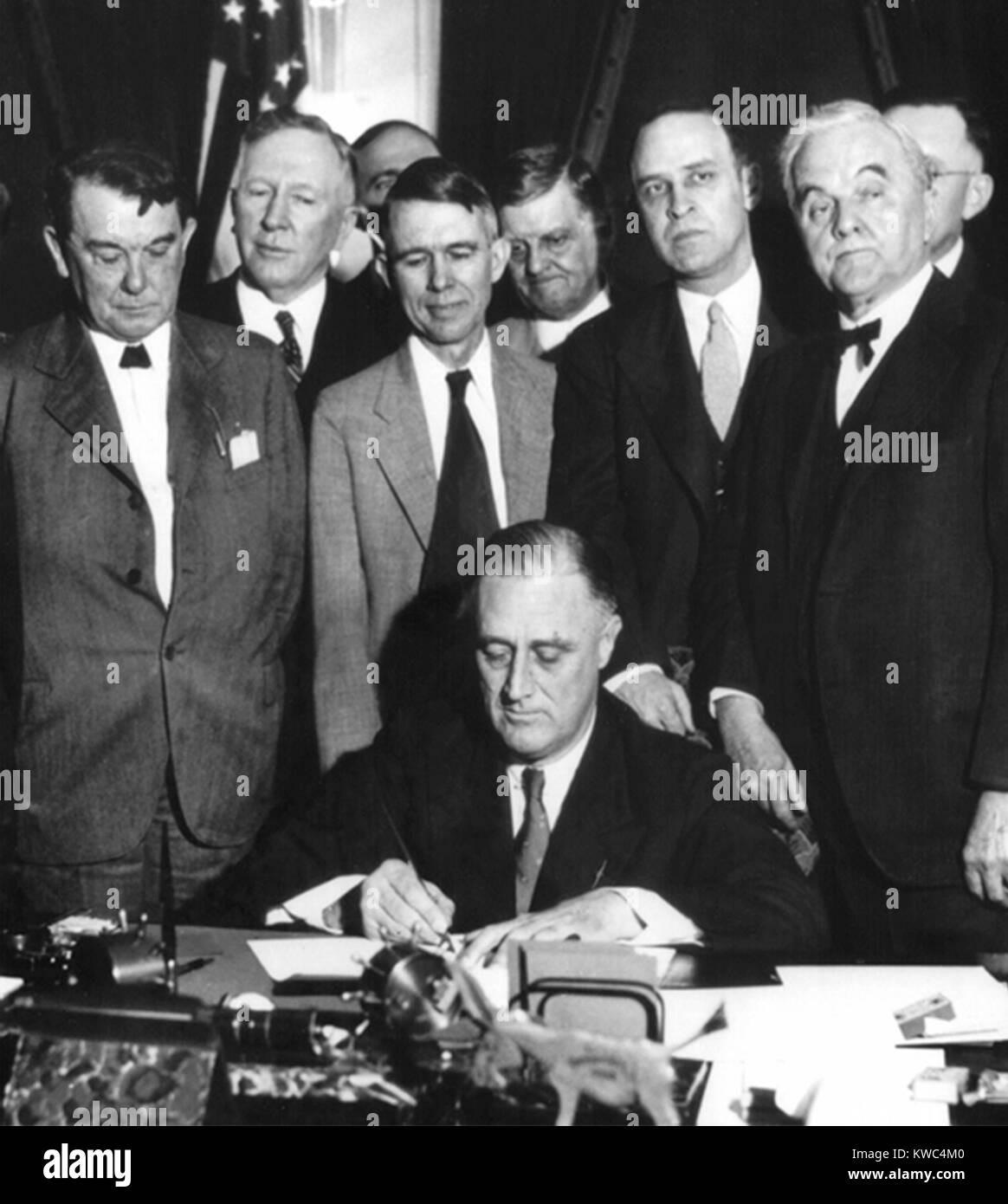 President Franklin D. Roosevelt signs the TVA Act, on May 18, 1933. At right is Senator George Norris, whose bill - Stock Image