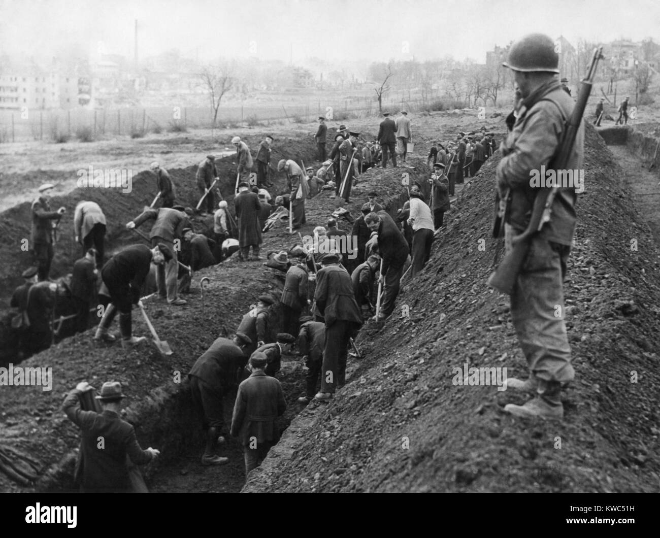 U.S. Soldier guards the reburial of concentration camp victims by German civilians. Ca. April-May 1945. Unidentified - Stock Image