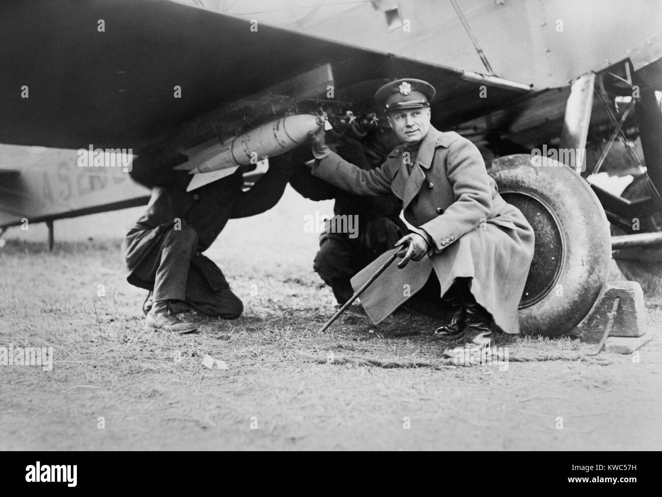 Brigadier General Billy Mitchell and another man, attaching a bomb under wing of airplane. Ca. 1925. He advocated - Stock Image
