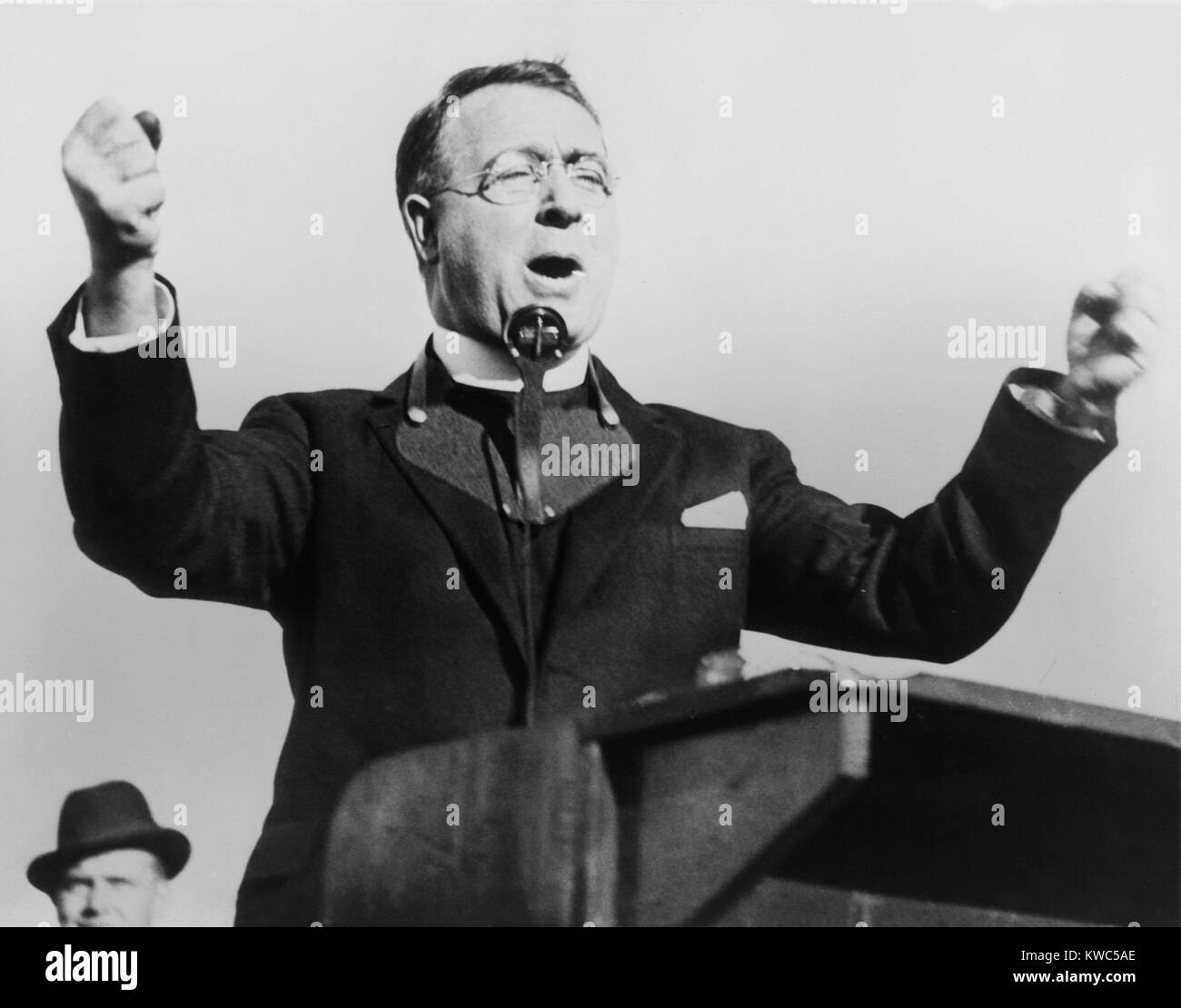 Charles Coughlin, with fists raised, attacks the New Deal in Boston, 1936. Wearing a microphone around his neck, - Stock Image