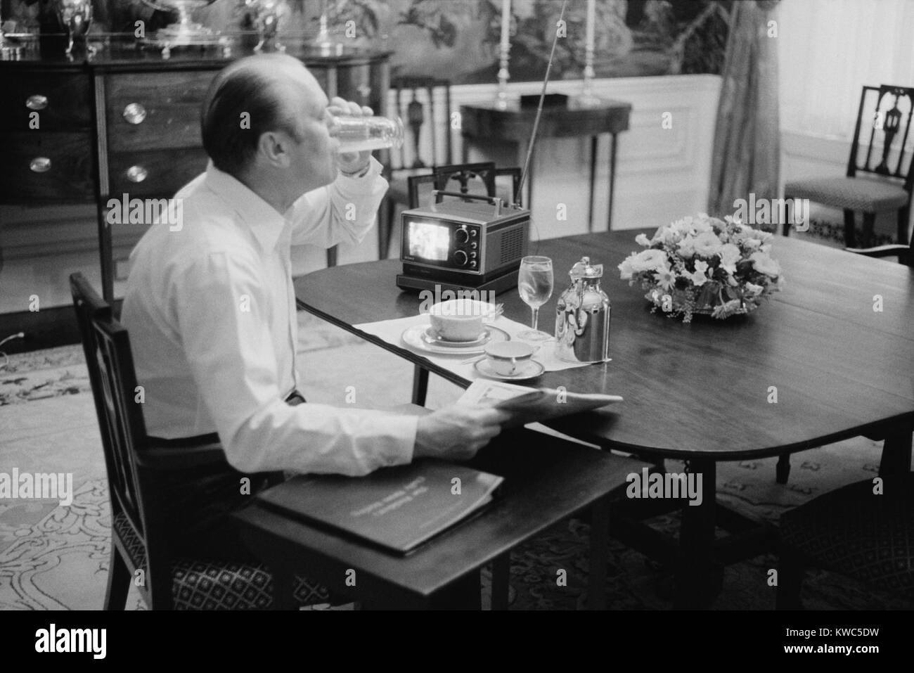 President Gerald Ford eating breakfast at the White House, Feb. 6, 1975. His 4 x 5 inch portable TV was the latest - Stock Image