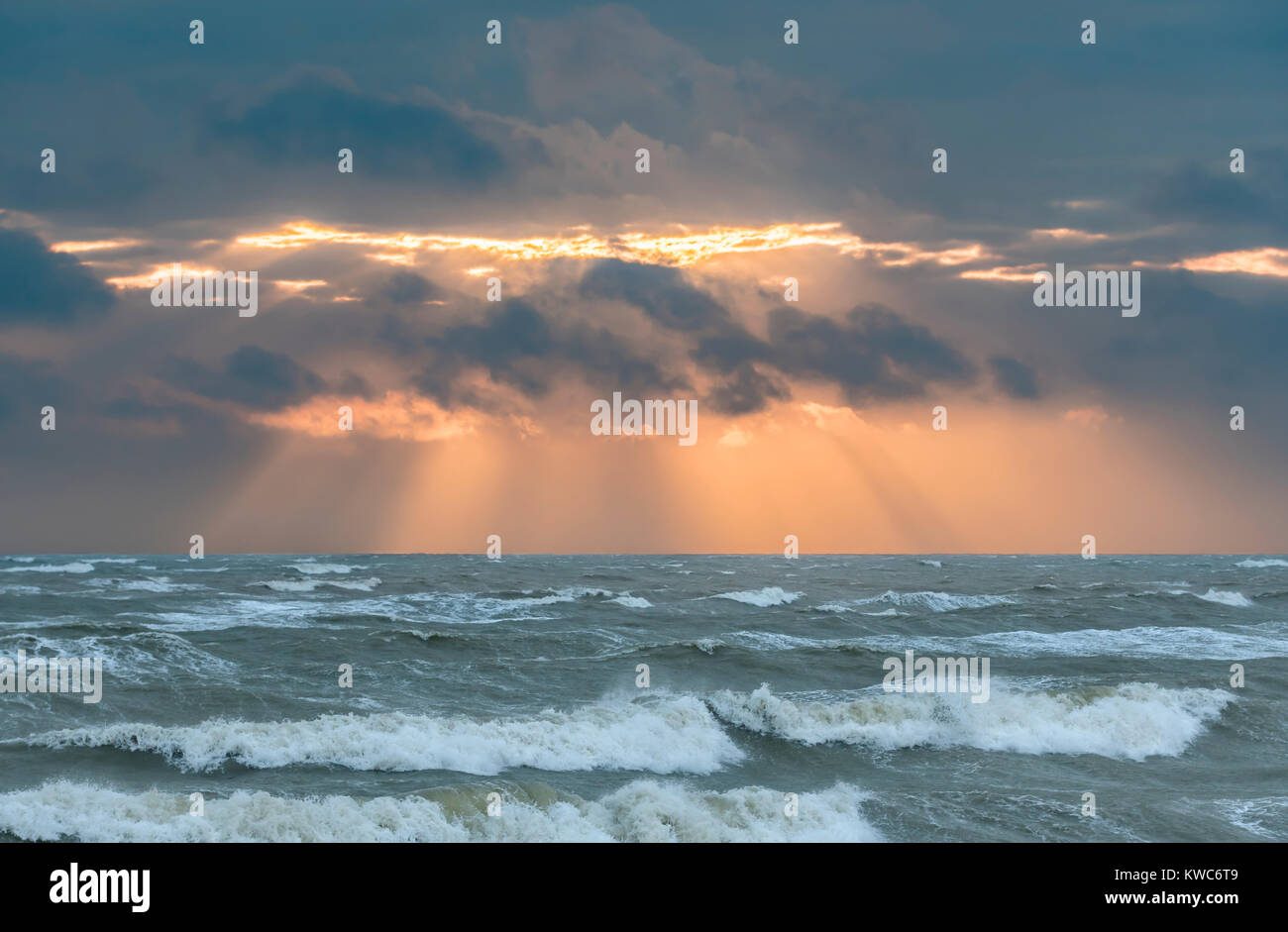 Low sun hidden by clouds with suns rays showing over a rough sea in Winter in the UK. - Stock Image