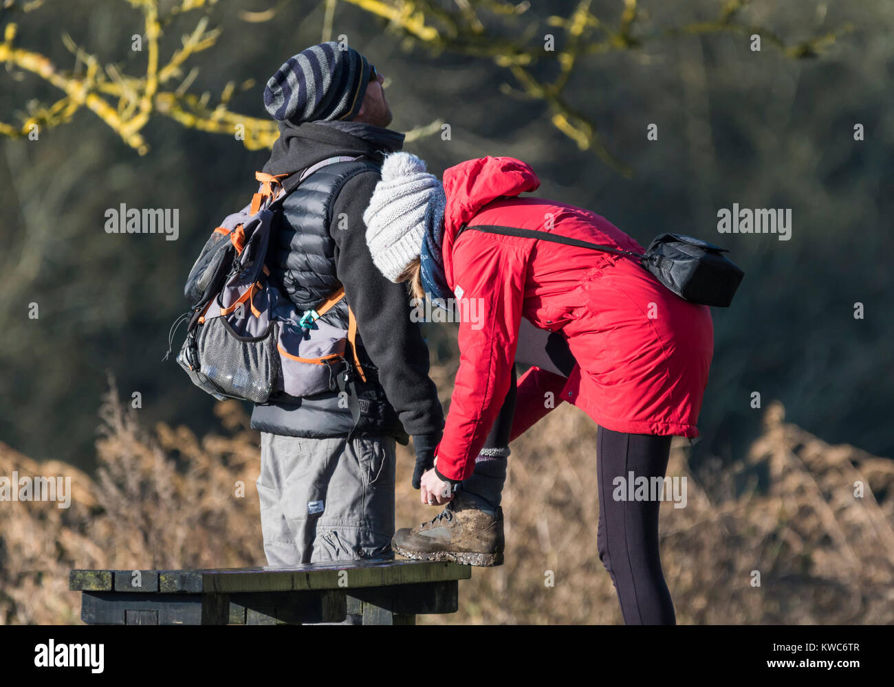 Woman stopping to tie walking boot shoe laces up after coming untied. - Stock Image