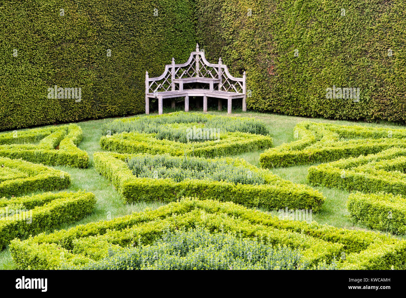 Antony House, Torpoint, Cornwall, UK. The secluded Knot Garden, with its ornate wooden bench - Stock Image